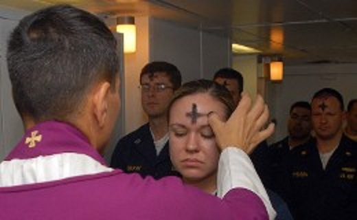 Electronics Technician 3rd Class Leila Tardieu receives the sacramental ashes during an Ash Wednesday celebration aboard the amphibious assault ship USS Wasp (LHD 1). U.S. Navy photo by Mass Communication Specialist 3rd Class Brian May (Released)